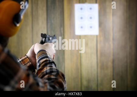 man with put on protective goggles and ear training in pistol sh - Stock Photo