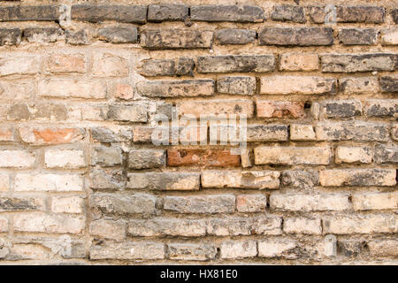 Background of old vintage dirty brick wall with peeling plaster - Stock Photo