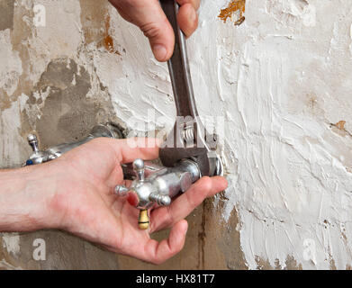 Close-up of hands plumbing unscrew connecting nut wall faucet using an adjustable wrench. - Stock Photo