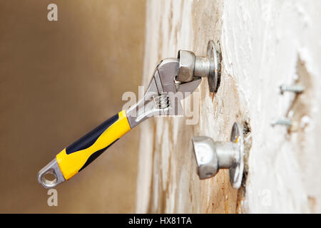 Closeup wall mount faucet eccentric adjusts position with plumbers adjustable wrench. - Stock Photo