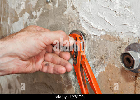Repair wall mount faucet, close-up hand plumber turns eccentric tap using red pliers. - Stock Photo