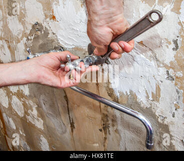 Dismantling of old faulty faucet, close-up hands of plumber with adjustable wrench. - Stock Photo