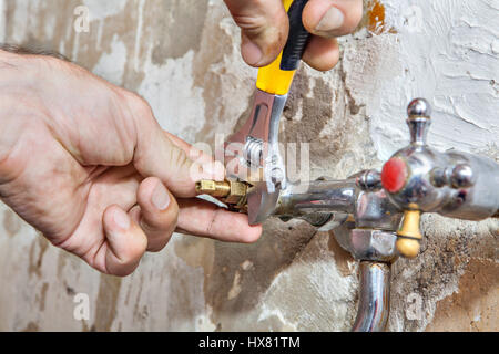 Kitchen faucet repair,  valve tap replacement, close-up adjustable wrench in hand plumbing. - Stock Photo