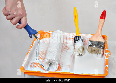House painting supplies, painter tools in an orange tray with white paint, roller brush and  paintbrushes. - Stock Photo