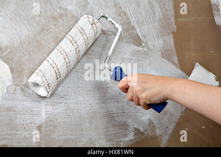 Close-up hand holds rolling paint brush, painting interior stucco wall with white color. - Stock Photo