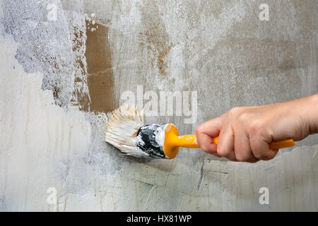 Close-up, paint brush with yellow plastic handle in a hand painter, repainting the green wall in white. - Stock Photo