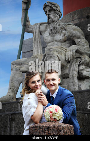 Russia, Saint-Petersburg, bride and groom stand near Rostral column, against the sculpture. - Stock Photo