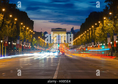 Night view of Paris traffic in Champs-Elysees street and the Arc de Triomphe in Paris, France. - Stock Photo