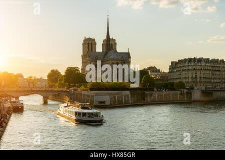 Notre Dame de Paris with cruise ship on Seine river in Paris, France - Stock Photo