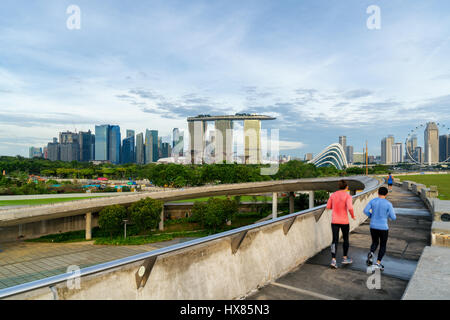 People jogging at morning in Singapore. Singapore Downtown Core in the background. - Stock Photo