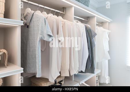 Modern interior wardrobe with shirt and dress in shelf. - Stock Photo