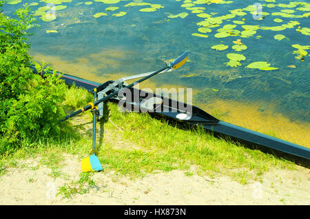 Single academy rowing boat on the beach - Stock Photo