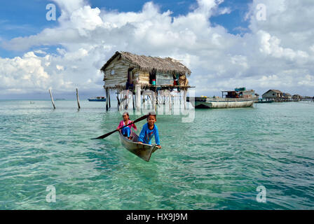 SEMPORNA SABAH, MALAYSIA - APRIL 19, 2015: Bajau Laut children paddle in boats near stilted houses in The Celebes - Stock Photo