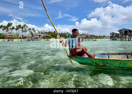 SEMPORNA SABAH, MALAYSIA - APRIL 19, 2015: Young girl of Bajau laut paddling a boat near Bajau Laut village in Maiga - Stock Photo