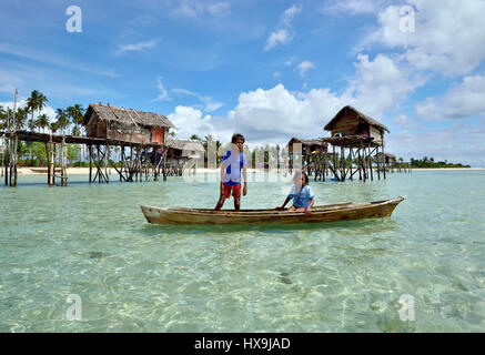 SEMPORNA SABAH, MALAYSIA - APRIL 19, 2015: Bajau laut kids paddling on a boat near Bajau Laut village in Maiga Island - Stock Photo