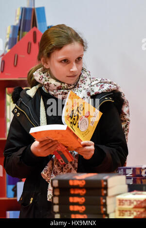 Paris, France. 25th Mar, 2017. A girl browses a book during the 37th Paris Book Fair in Paris, France, on March - Stock Photo