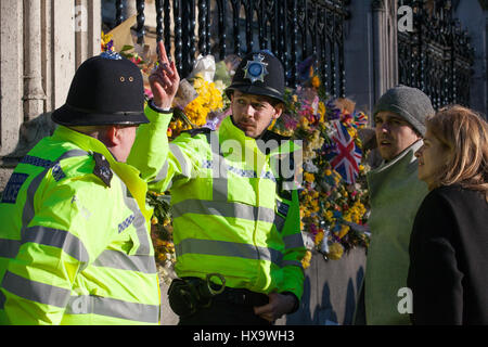 London, UK. 25th Mar, 2017. Police officers stand at the gates of the Palace of Westminster alongside Spring flowers - Stock Photo
