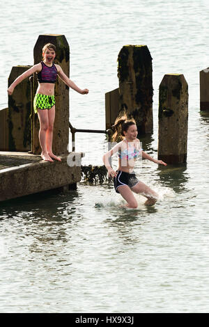 Aberystwyth, Wales UK, Mothers Day, Sunday 26 March 2017 UK weather: Kids jumping into the sea off the wooden pier - Stock Photo