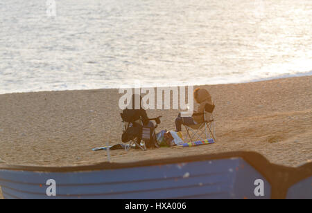 Burton Bradstock, Dorset, UK. 26th March 2017. Two women enjoy a glass of wine wrapped up in their clothes on a - Stock Photo