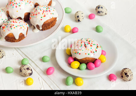 Easter cakes with white icing and easter festive decor on white background with copy space - homemade festive pastry - Stock Photo