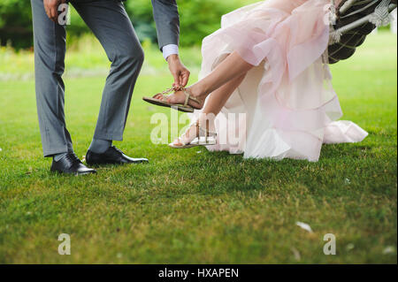 Groom helping bride to put on shoe outdoors - Stock Photo