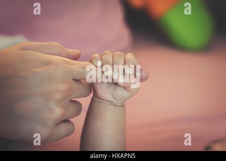 Newborn baby touching his mother hand - Stock Photo