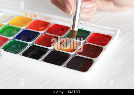 process of Painting with watercolors, a palette and brush in hand - Stock Photo