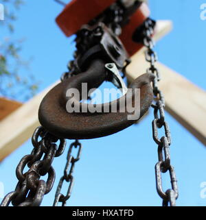 Old rusty hook on blue sky background. Construction industry. - Stock Photo
