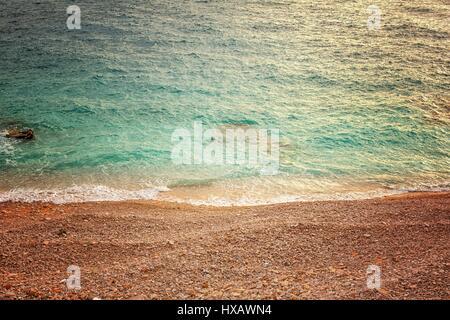 Sea and polished rocks on the shore closeup - Stock Photo