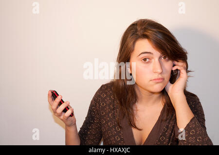 Young woman using two mobile phones. - Stock Photo