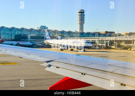 View of the Tampa, Florida airport terminal and control tower from taxiing Southwest Airlines jet on runway with - Stock Photo