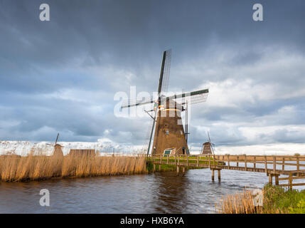 Amazing windmills. Rustic landscape with traditional dutch windmills, bridge near the water canals and blue cloudy - Stock Photo