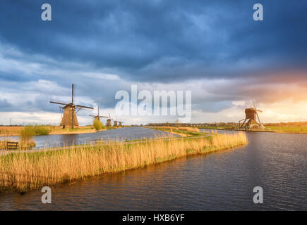 Amazing windmills. Rustic landscape with traditional dutch windmills near the water canals and blue cloudy sky and - Stock Photo