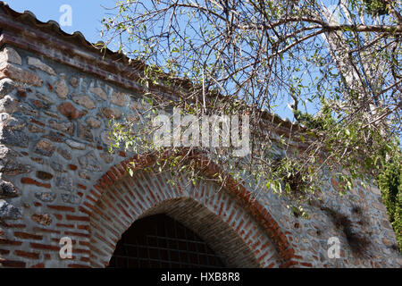 Fragment of restored medieval mosque with arch built from stone and brick with tree branches entering frame - Stock Photo