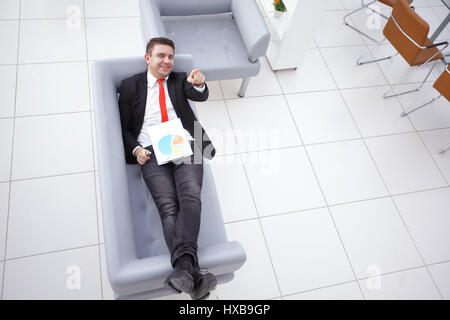 Businessman lying on sofa and smiling at camera in the office - Stock Photo
