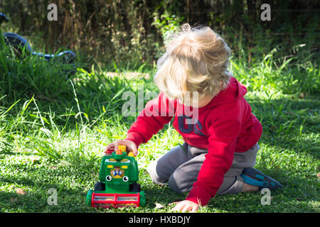 Little boy playing with toy harvester underneath trees outdoors - Stock Photo