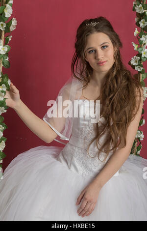 Charming bride sitting on a swing. - Stock Photo