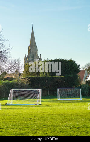 Looking across a playing field with football goals in the foreground and a church with a spire in the background. - Stock Photo
