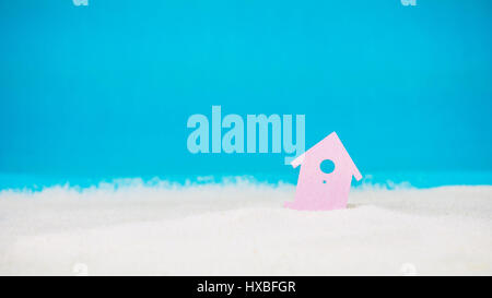 Symbol of little lilac house on the sand with bright blue background - Stock Photo