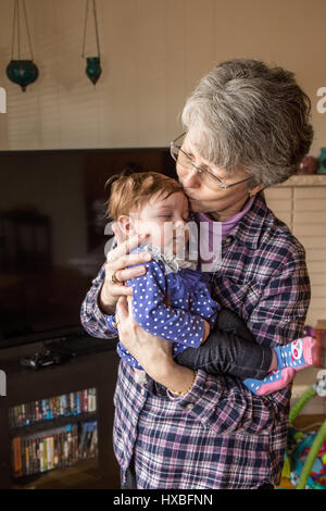 Grandmother hugging her three month old granddaughter - Stock Photo