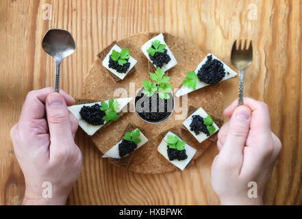 snack black caviar on a wooden background - Stock Photo