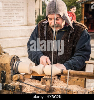 Trento, Italy - January 3, 2016: An artisan carves a piece of wood using an old manual lathe. - Stock Photo