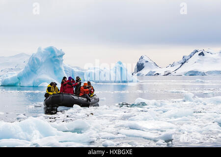 Antarctica tourists in Zodiac among Antarctic iceberg.