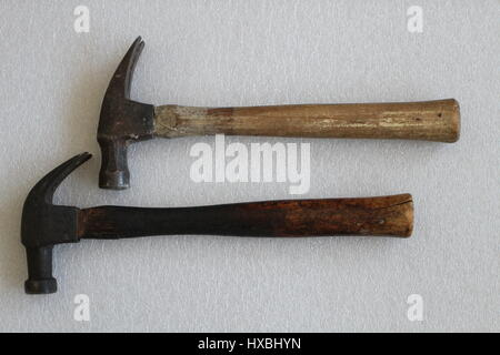 Two old iron hammers with wooden handles, lying on a white background and arranged horizontally. Old hammers made in the USA. Old but reliable tools.