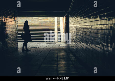 Silhouette of women against underground passage stairs leading up on the street - Stock Photo