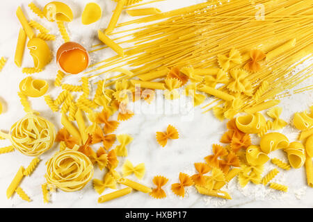 Various types of pasta on a white marble table with flour and an egg - Stock Photo