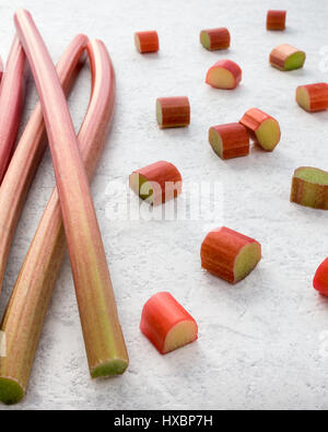 Fresh rhubarb and cut pieces of rhubarb on textured white marbled background. Shallow depth of field. - Stock Photo