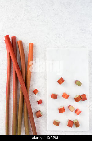 Fresh rhubarb and cut pieces of rhubarb on white marble chopping board. - Stock Photo
