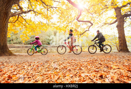 Young family bike riding in autumn park - Stock Photo