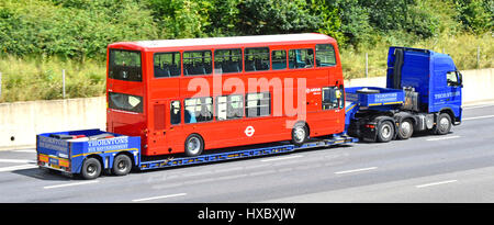 Arriva London bus red double decker  transportation on a low loader transporter travelling slowly transporting along - Stock Photo
